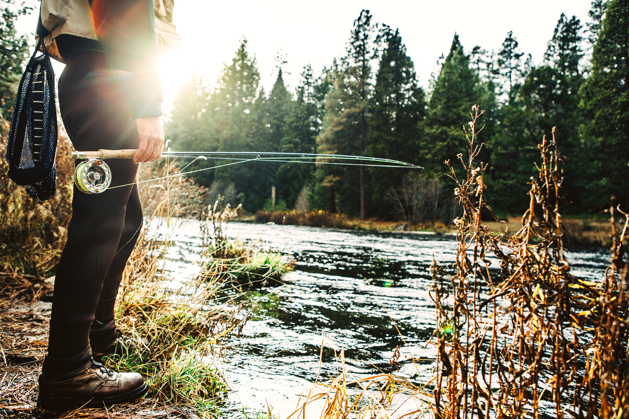 A fly fisherman views the Metolius river in central Oregon state, holding his rod and tackle. Emphasis and detail on the hand, pole and line. Horizontal with copy space.